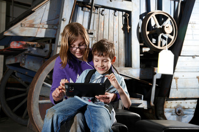 boy and young person communicating using an iPad in a museum