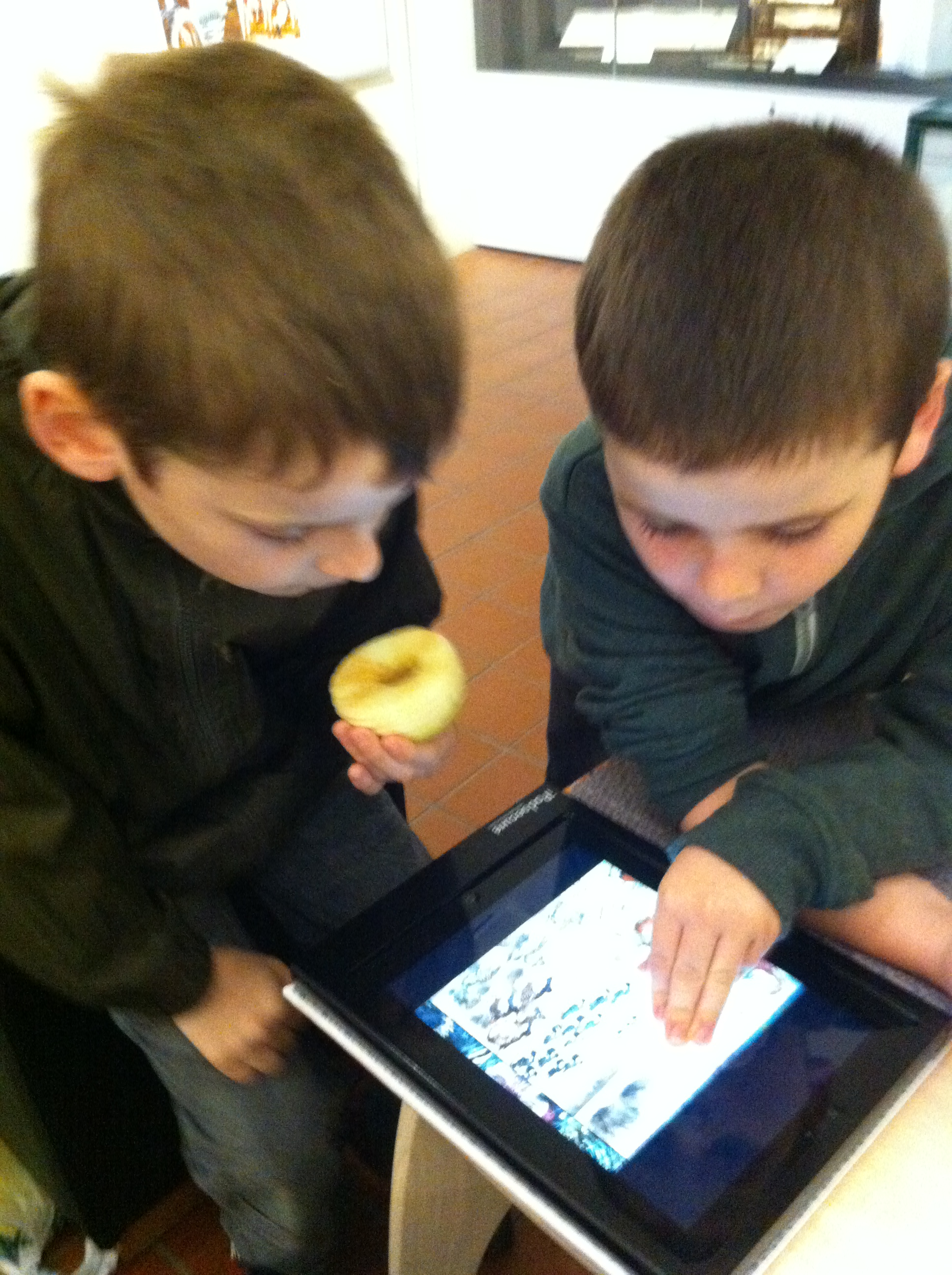 two boys using an ipad together